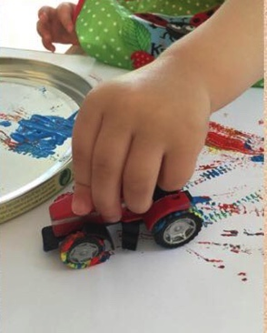 kid painting with a car