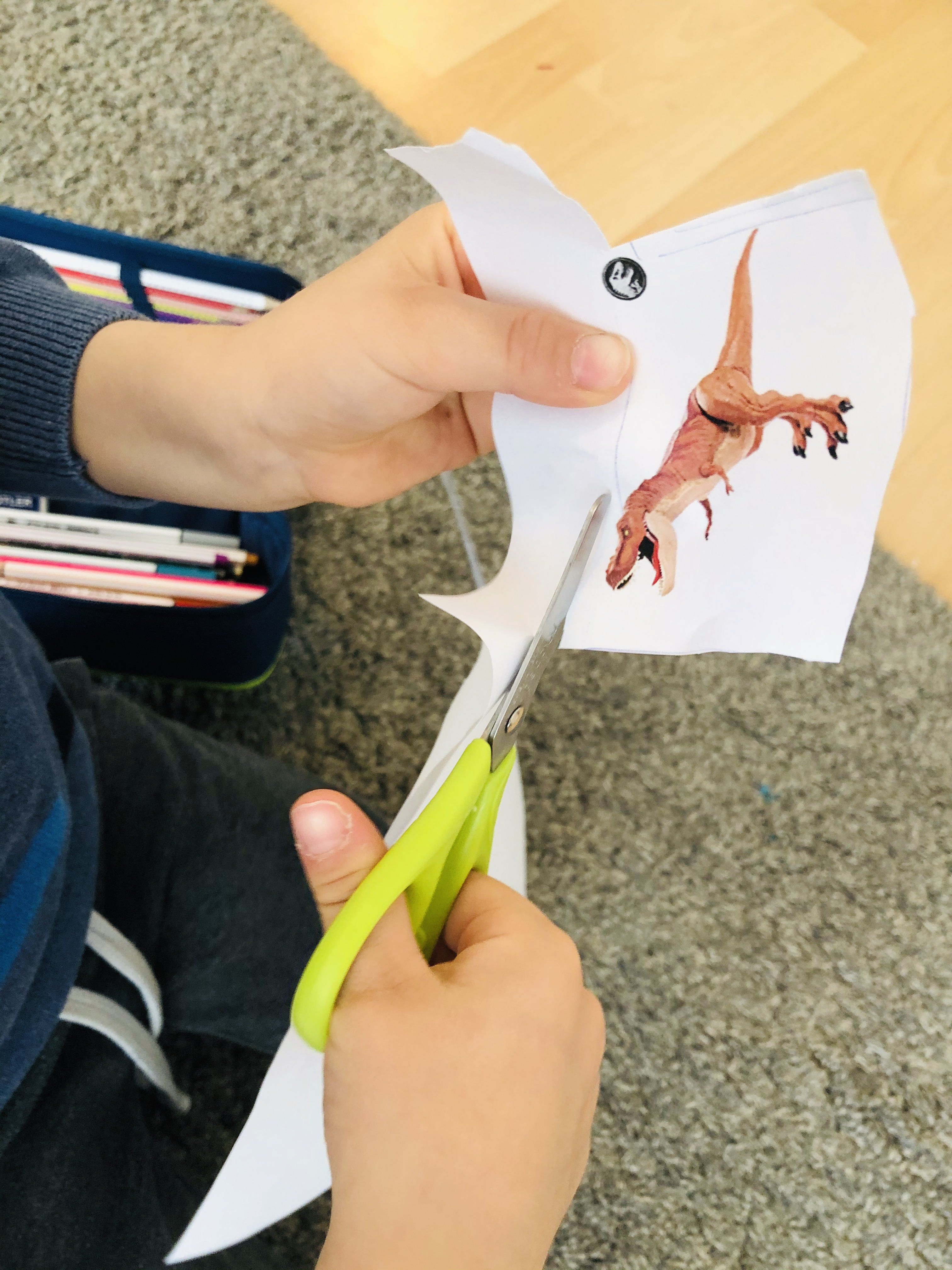 kid cutting out a dino for the numbers maze