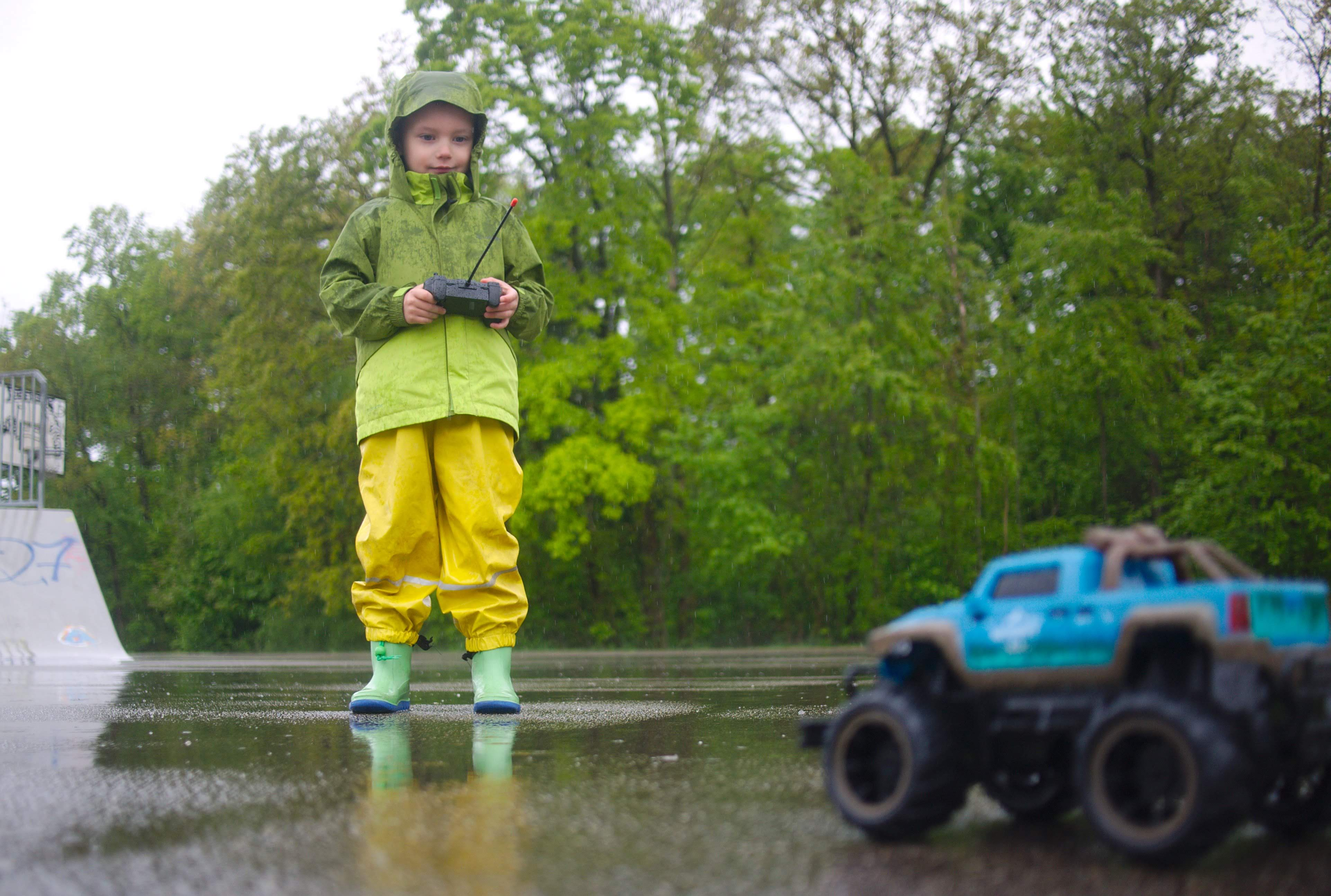 kid driving a remote car in rain