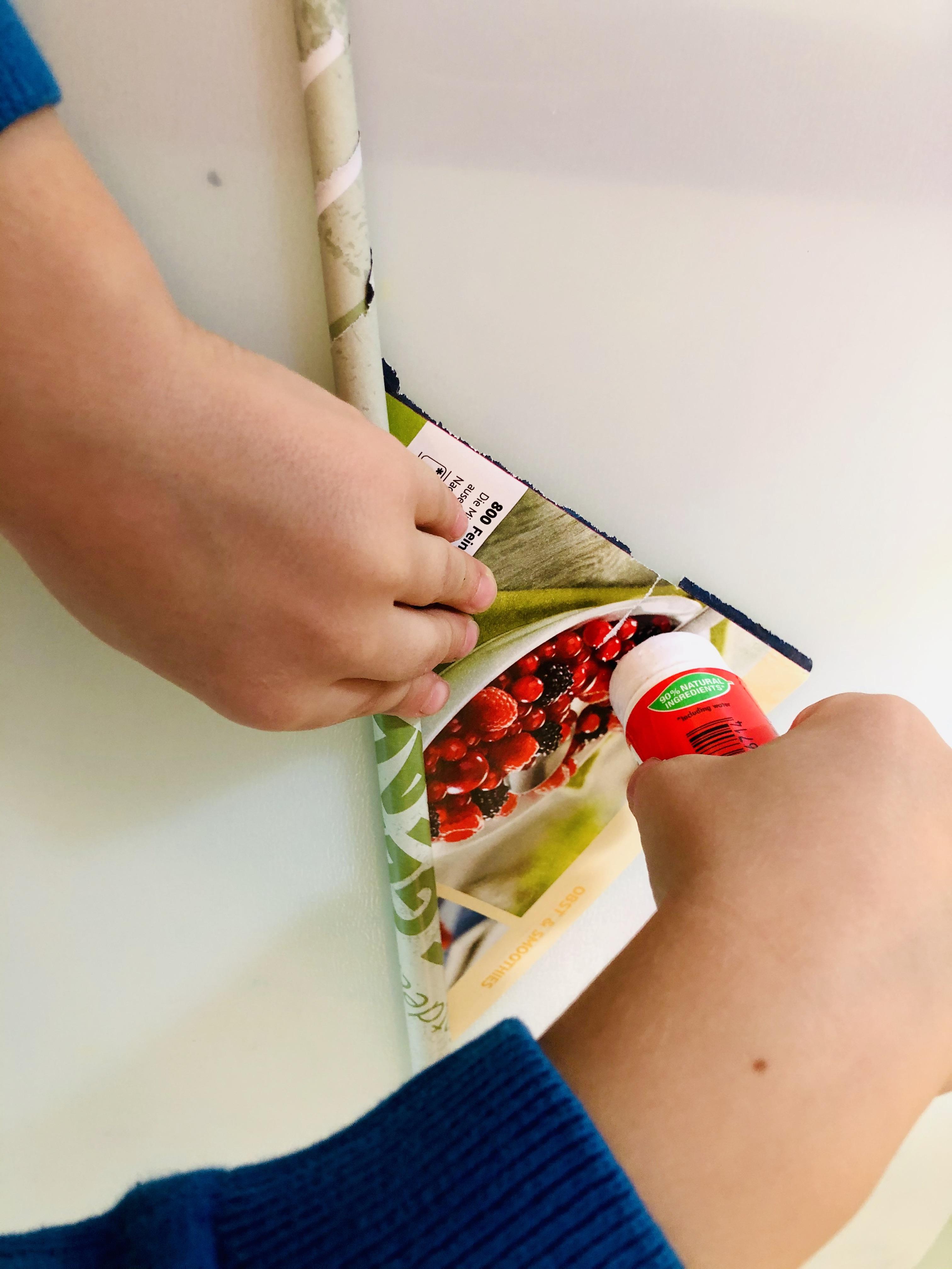 kid glueing old magazine paper rolls