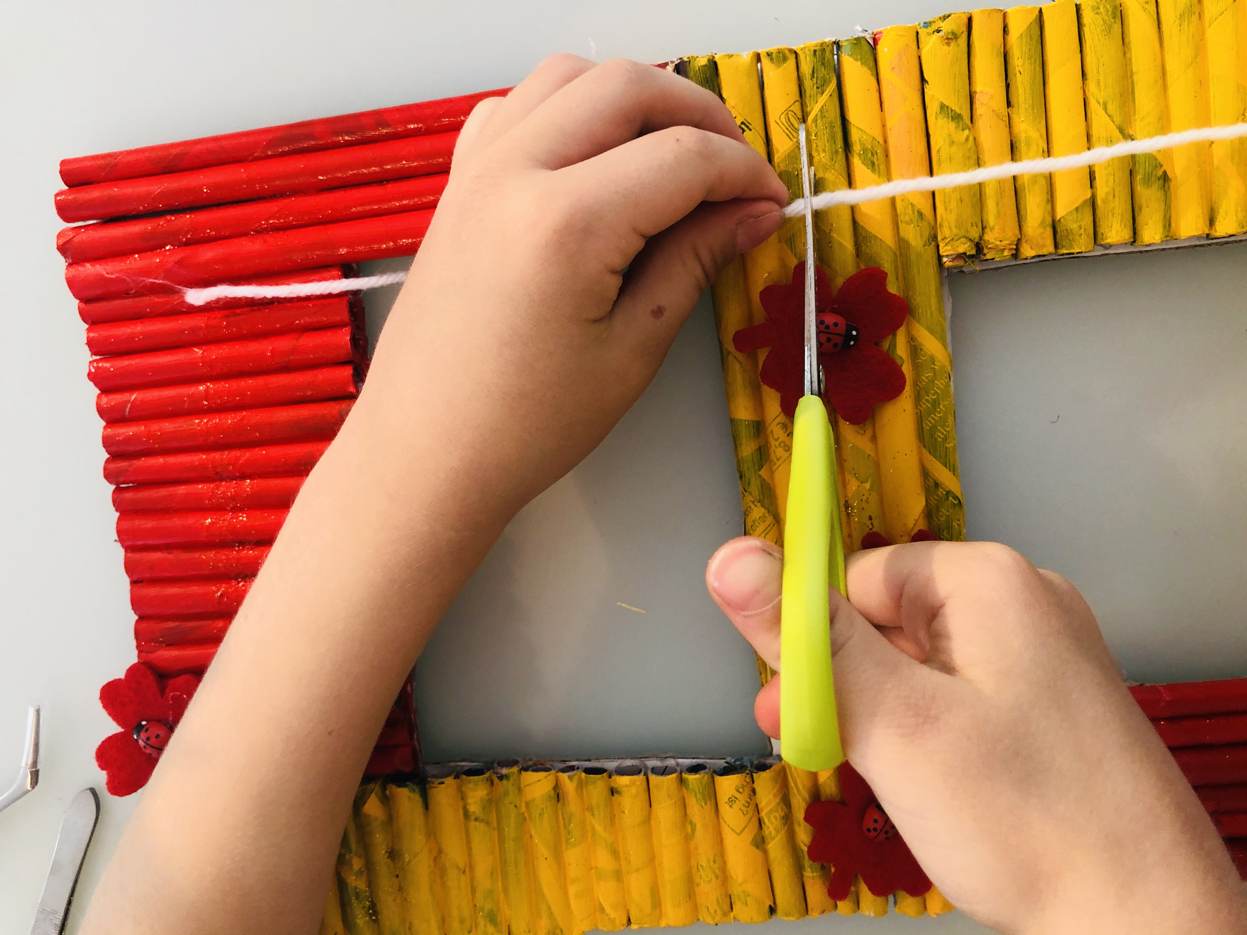 kid cutting a piece of wool string