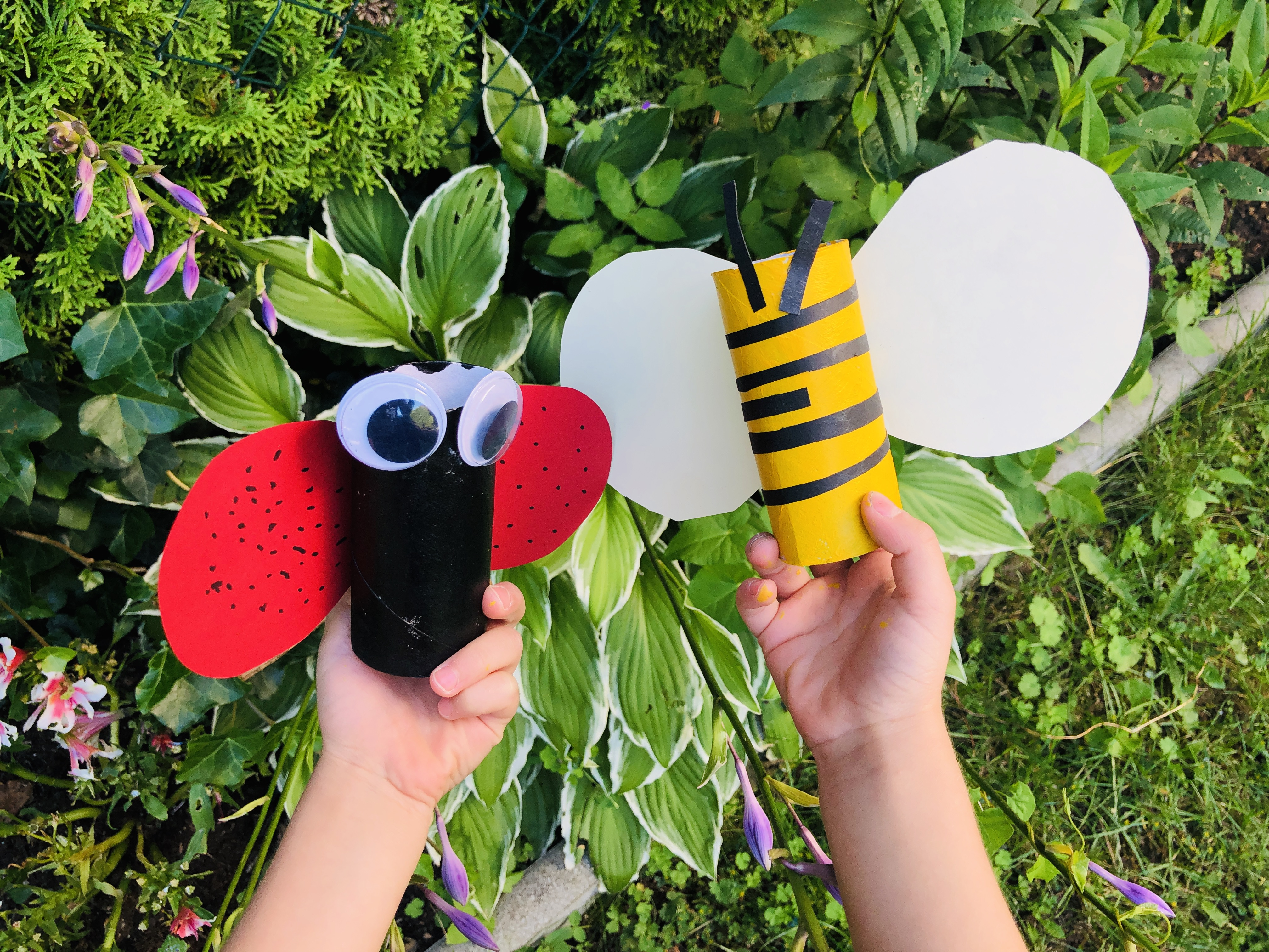 kid holding paper roll bee and ladybug