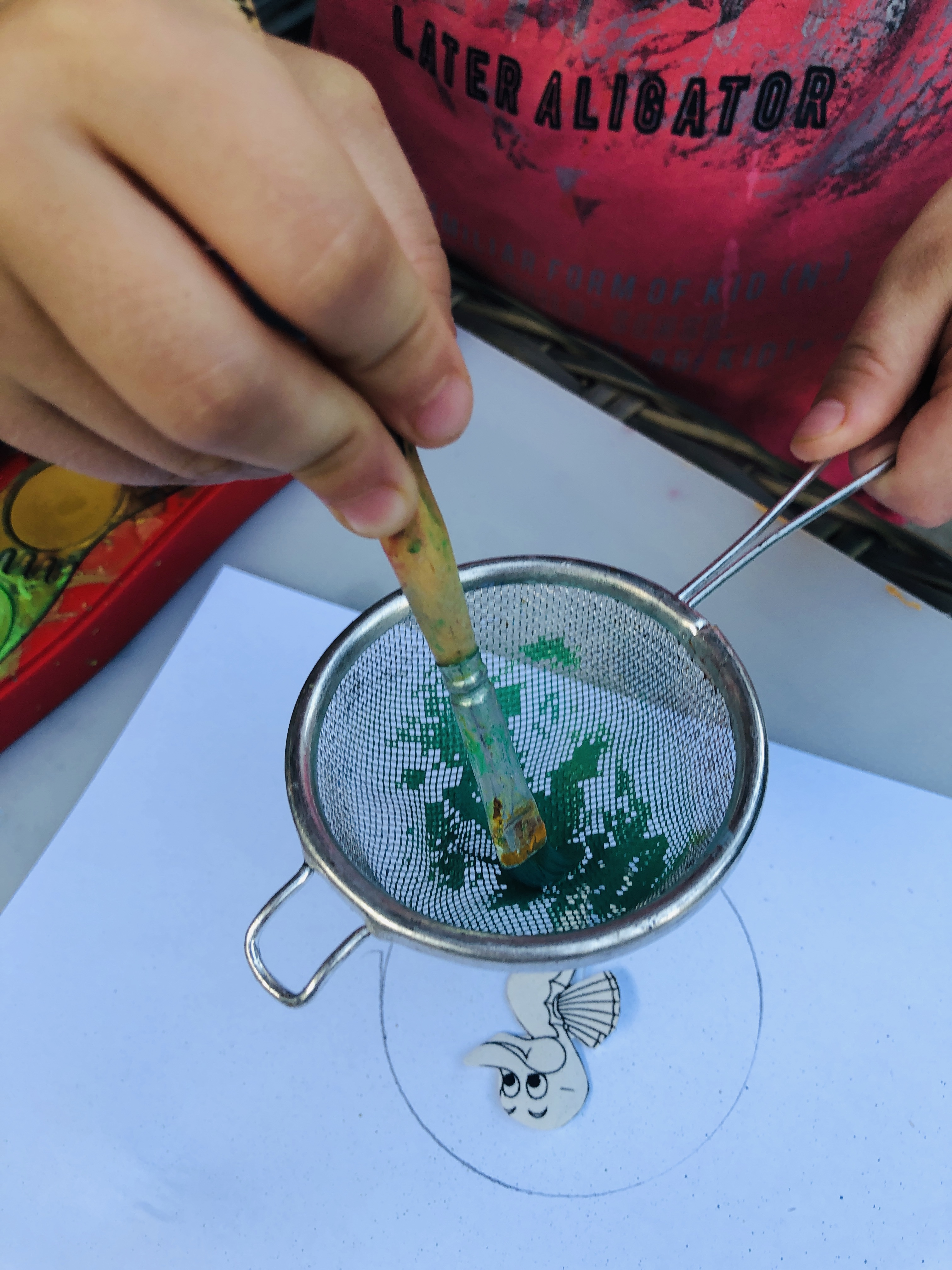 painting a seahorse using a hand colander