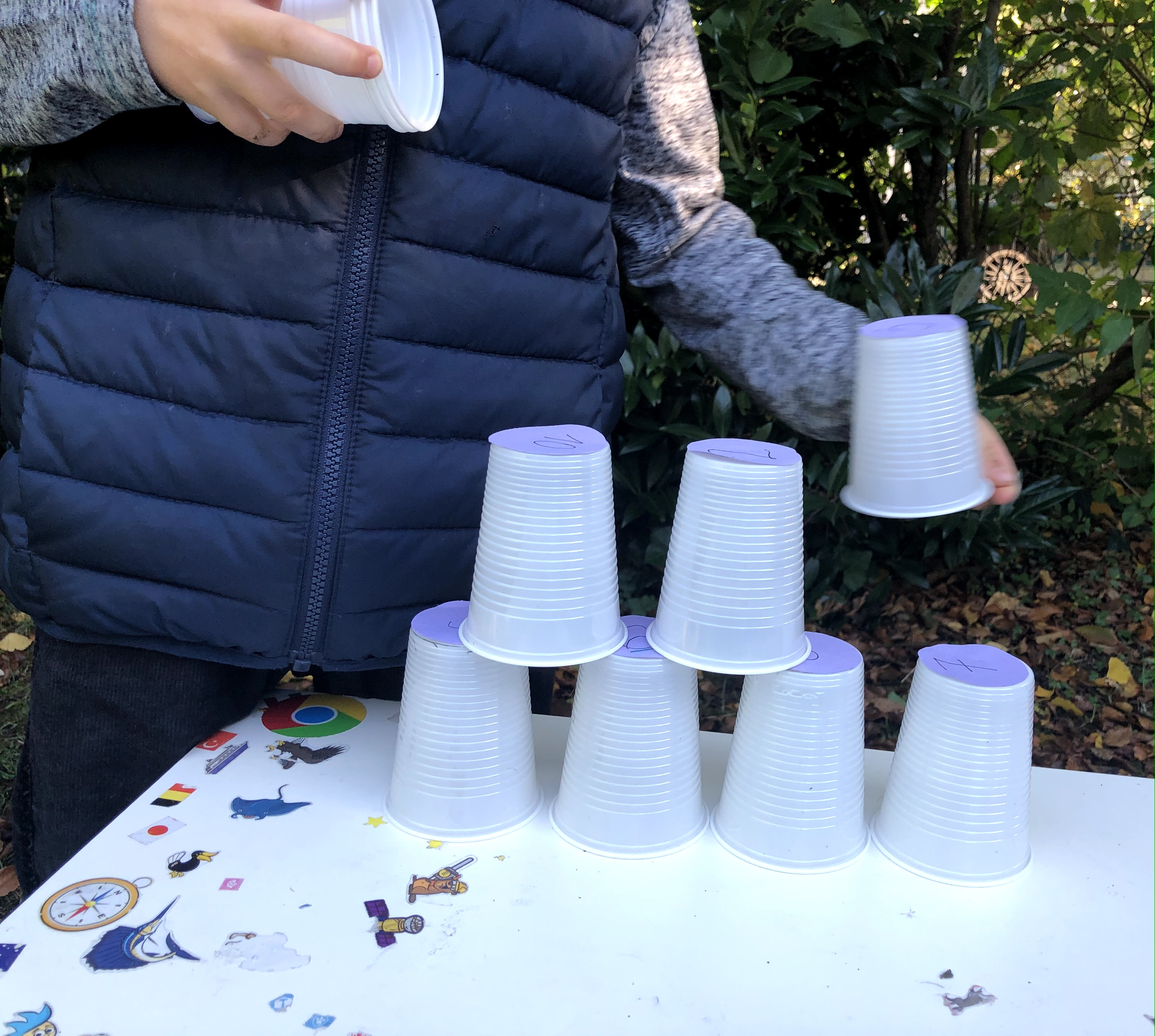 stacking plastic cups into a triangle