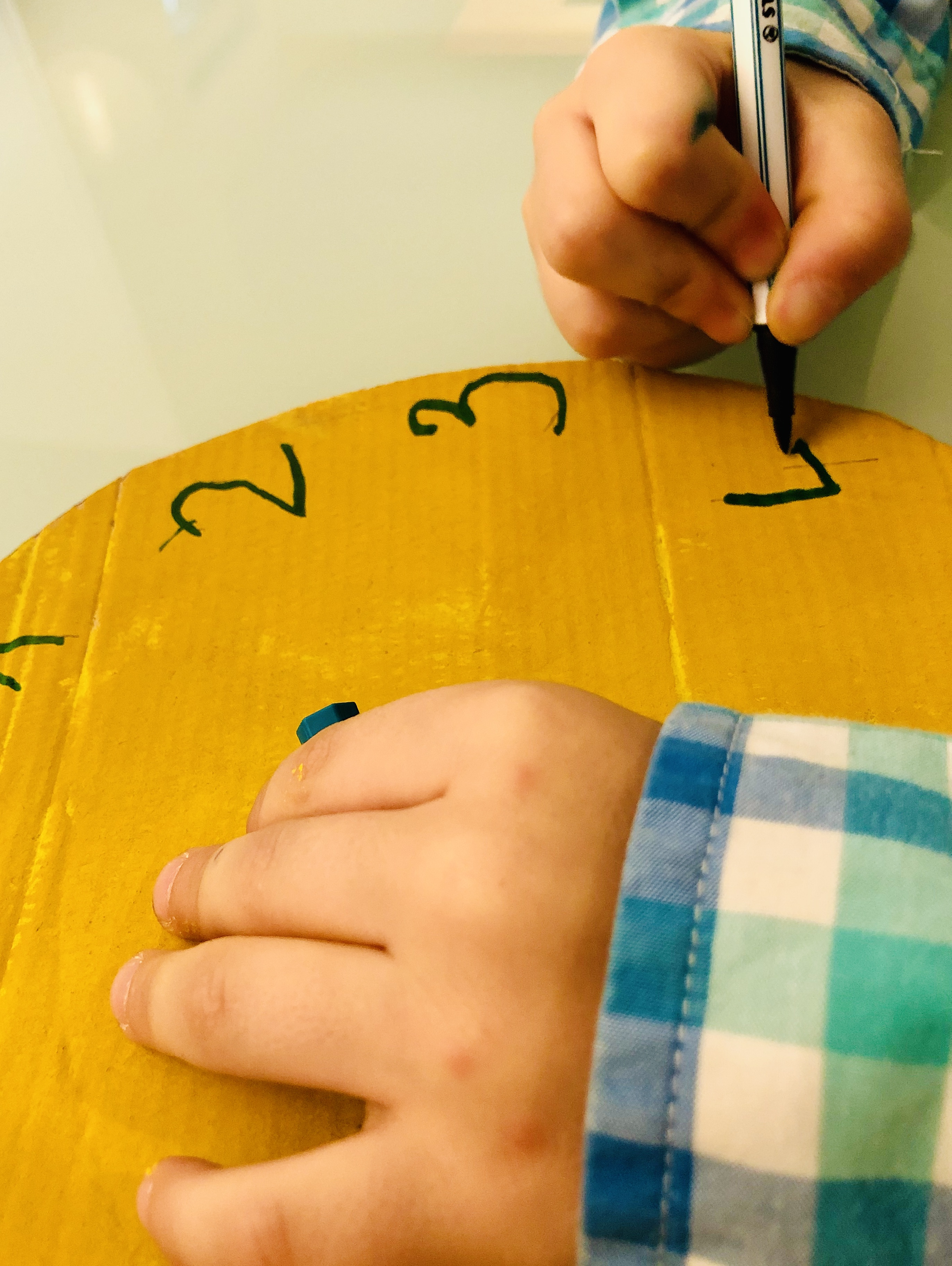 kid writing numbers on a clock