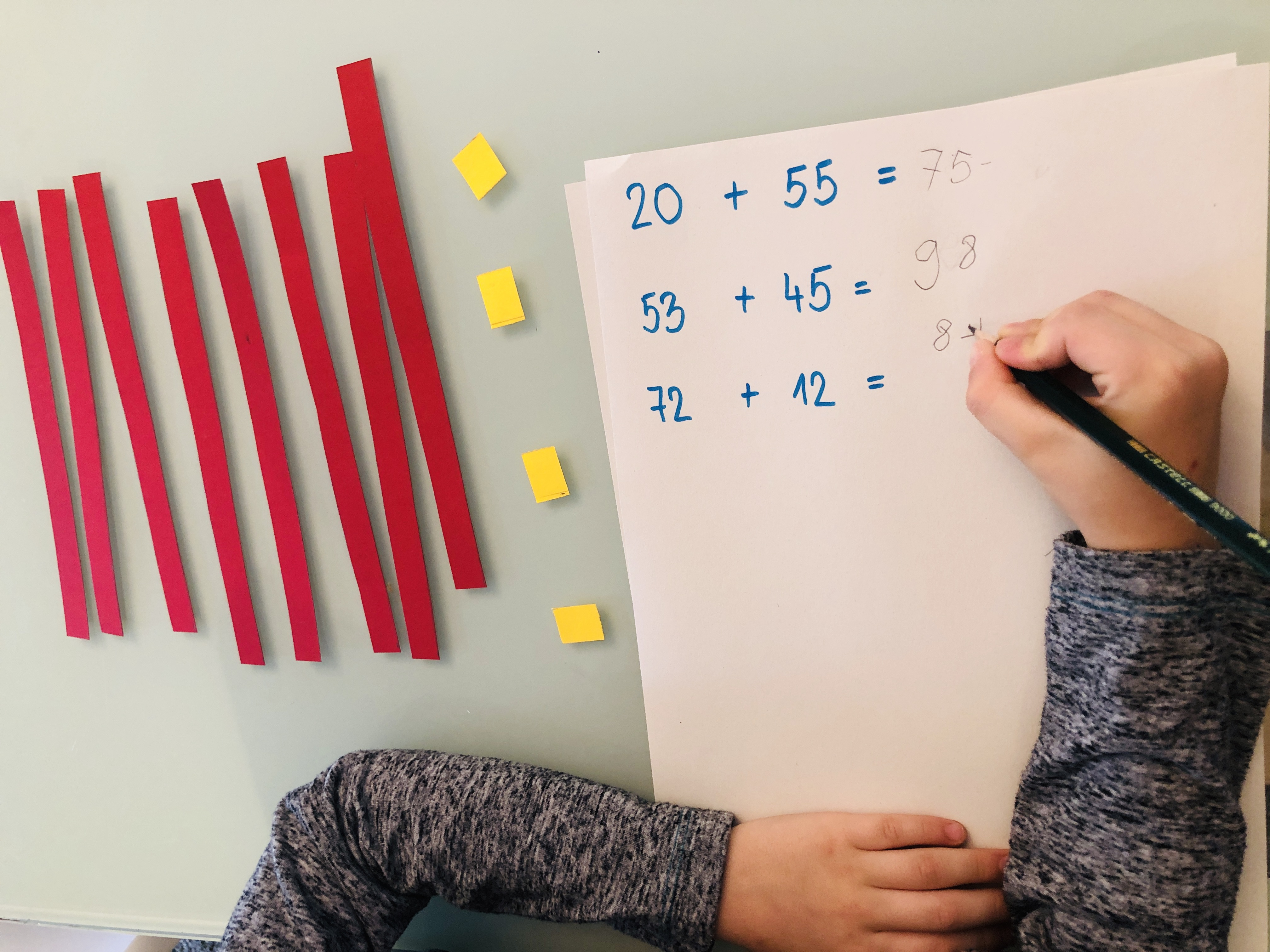 kid doing additions with two-digit numbers