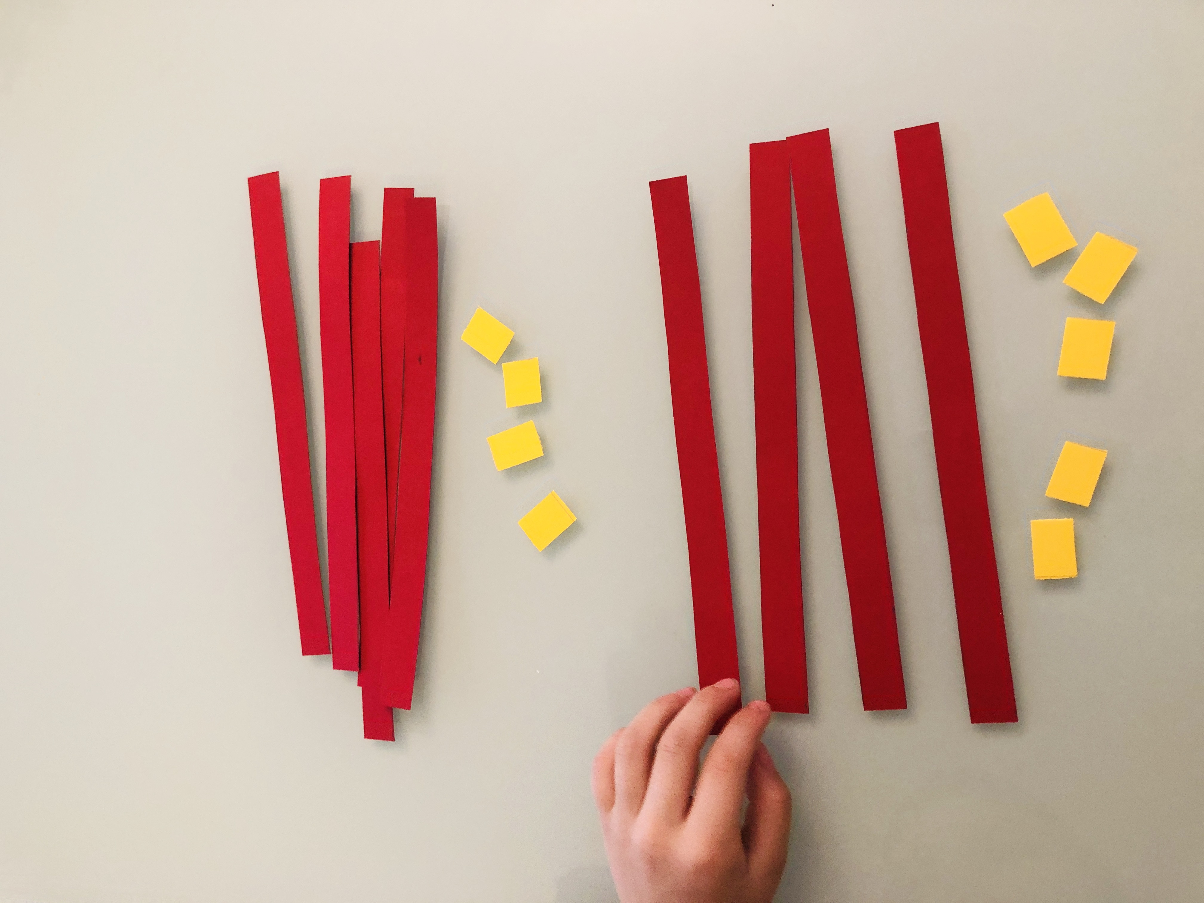 kid adding two-digit numbers using red and yellow cut-outs