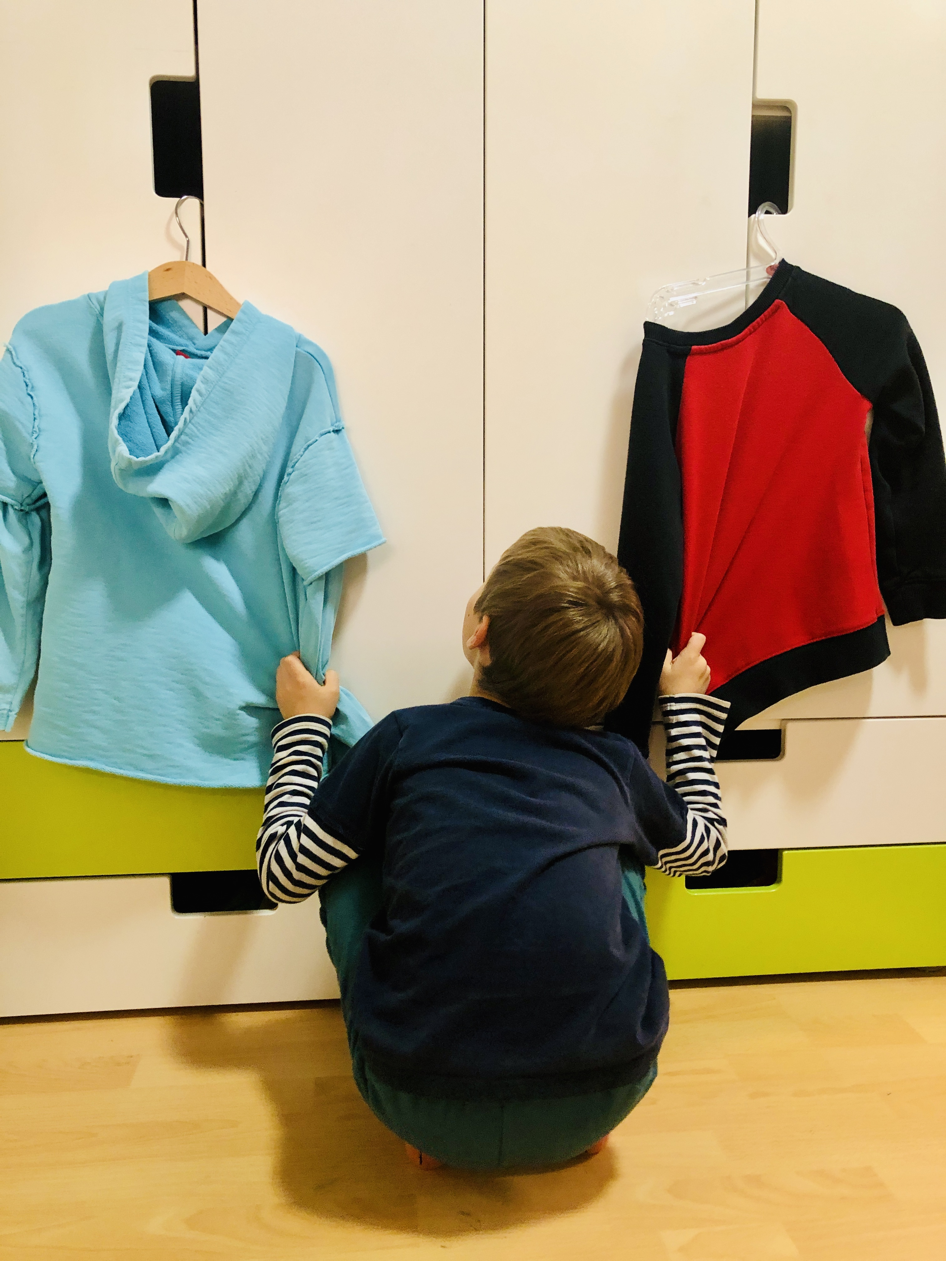 kid deciding which t-shirt to wear