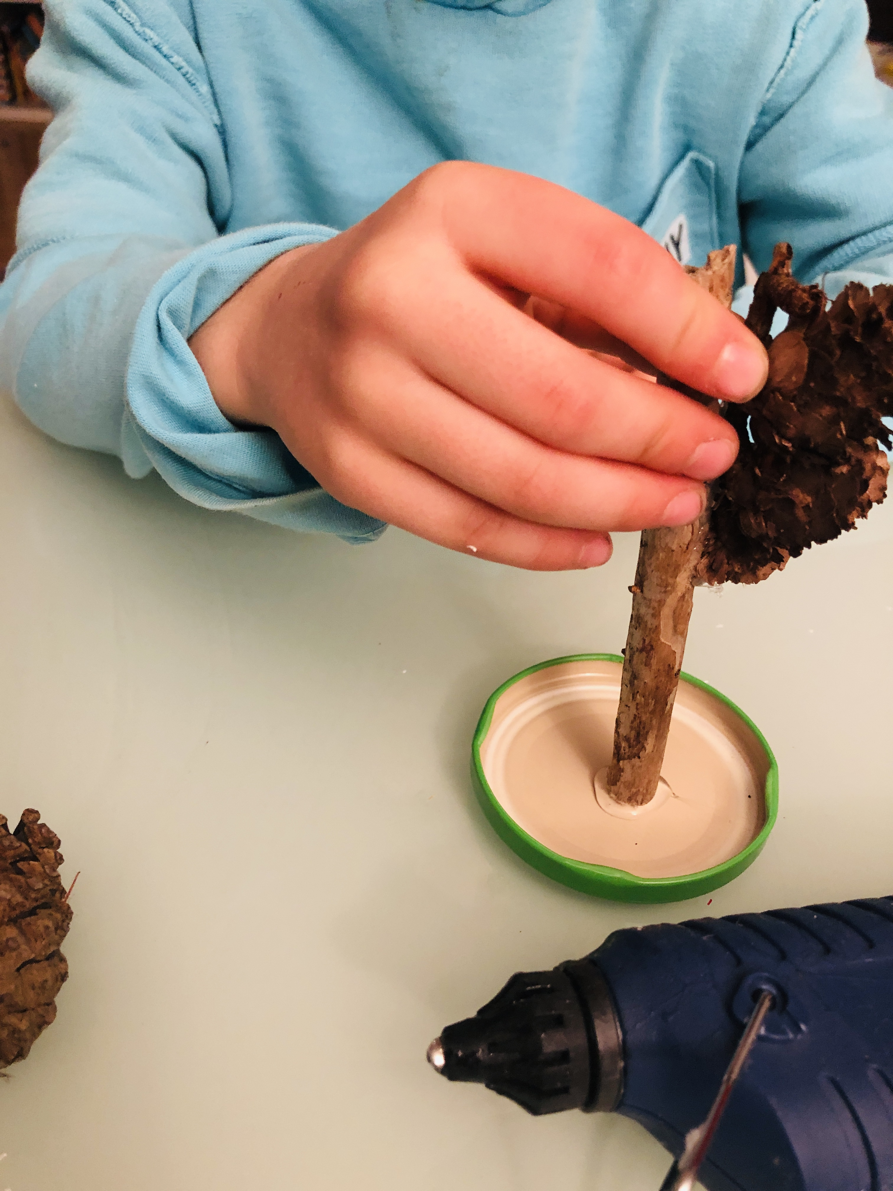 glueing the pine cones on the lid